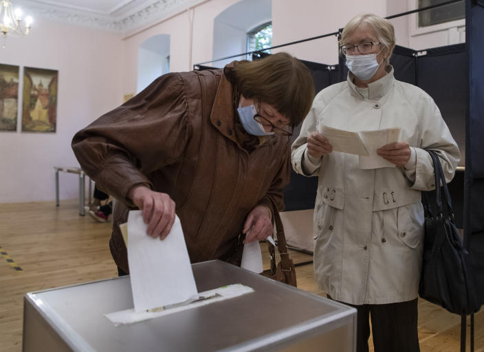 A Lithuanian woman, wearing face masks to protect against coronavirus cast their ballots at a polling station during parliamentary elections in Vilnius, Lithuania, Sunday, Oct. 11, 2020. Polls opened Sunday for the first round of national election in Lithuania, where voters will renew the 141-seat parliament and the ruling four-party coalition is widely expected to face a stiff challenge from the opposition to remain in office. (AP Photo/Mindaugas Kulbis)