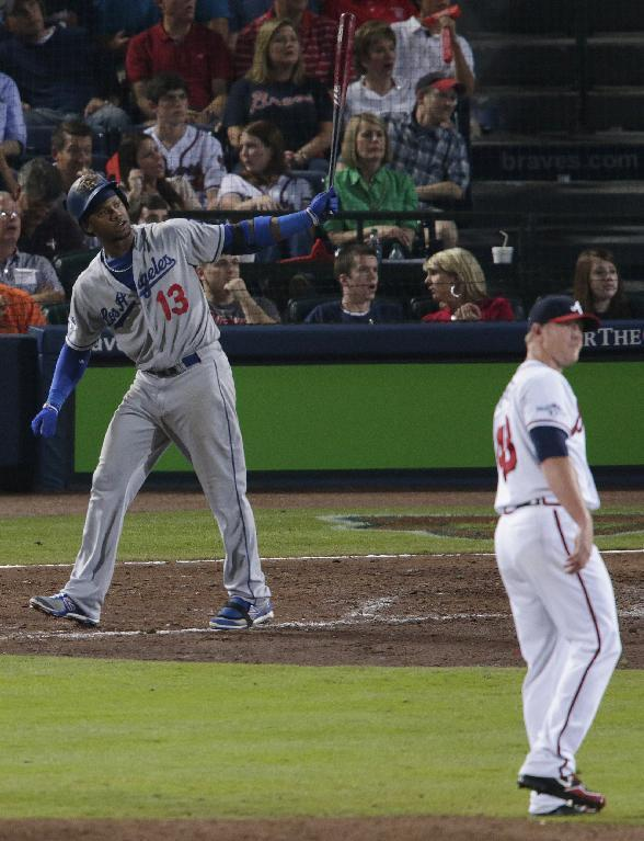 Los Angeles Dodgers' Hanley Ramirez (13) watches his two-run home run, scoring teammate Mark Ellis, as Atlanta Braves relief pitcher David Carpenter, right, look on during Game 2 of the National League division series on Friday, Oct. 4, 2013, in Atlanta. (AP Photo/Dave Martin)