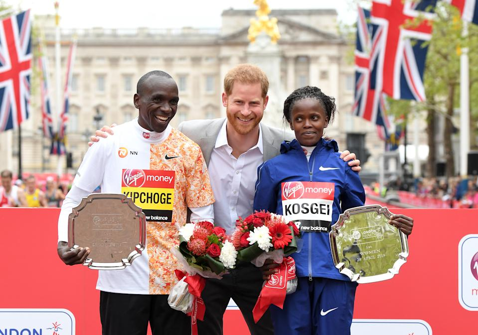 LONDON, ENGLAND - APRIL 28: Prince Harry, Duke of Sussex poses with Eliud Kipchoge (L), winner of the men's London marathon and Brigid Kosgei (R), winner of the women's London marathon during the medal ceremony at the Virgin London Marathon 2019 on April 28, 2019 in London, United Kingdom. (Photo by Karwai Tang/WireImage)