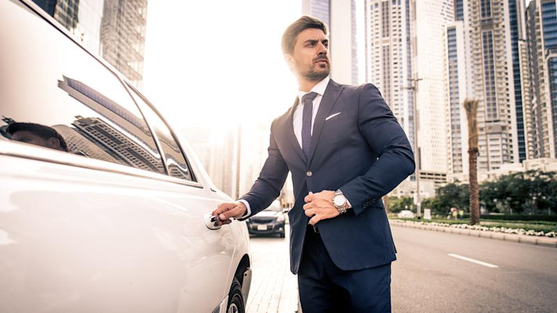 businessman getting into luxury limousine