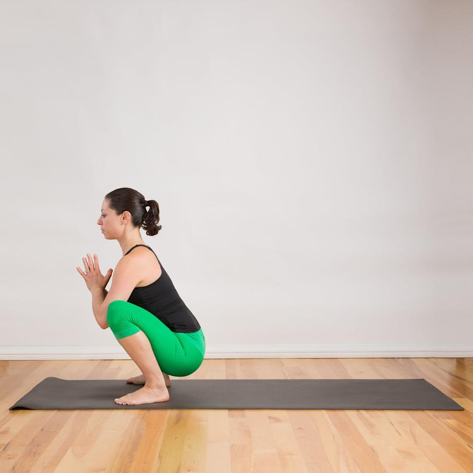 <ul> <li>Stand with your feet slightly wider than the hips.</li> <li>Bend your knees and lower your hips down toward the ground. If your heels don't touch the ground, roll up a towel or the back of your mat and place it under your heels for support. Also, widening your stance might make this pose feel easier.</li> <li>Rest your hands on the floor for support or bring your palms together at your heart center and firmly press your elbows against the inside of your knees. This will help to open your hips even further.</li> <li>Work on shifting weight into your heels and lengthening the crown of your head up toward the ceiling.</li> <li>Hold this pose for five deep breaths.</li> </ul>