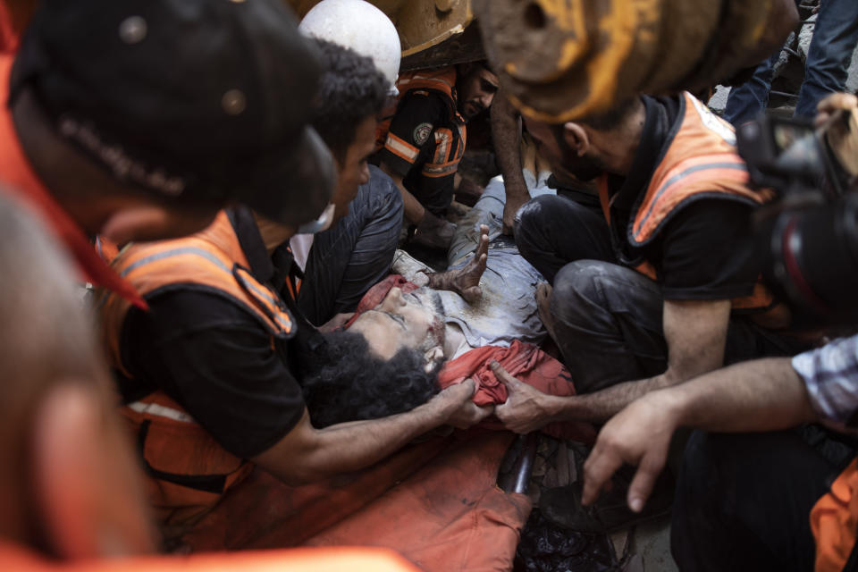 Palestinian rescuers pull a survivor man from under the rubble of a destroyed residential building following Israeli airstrikes in Gaza City, Sunday, May 16, 2021. The Israeli airstrikes flattened three buildings and killed at least 26 people Sunday, medics said, making it the deadliest single attack since heavy fighting broke out between Israel and the territory's militant Hamas rulers nearly a week ago. (AP Photo/Khalil Hamra)