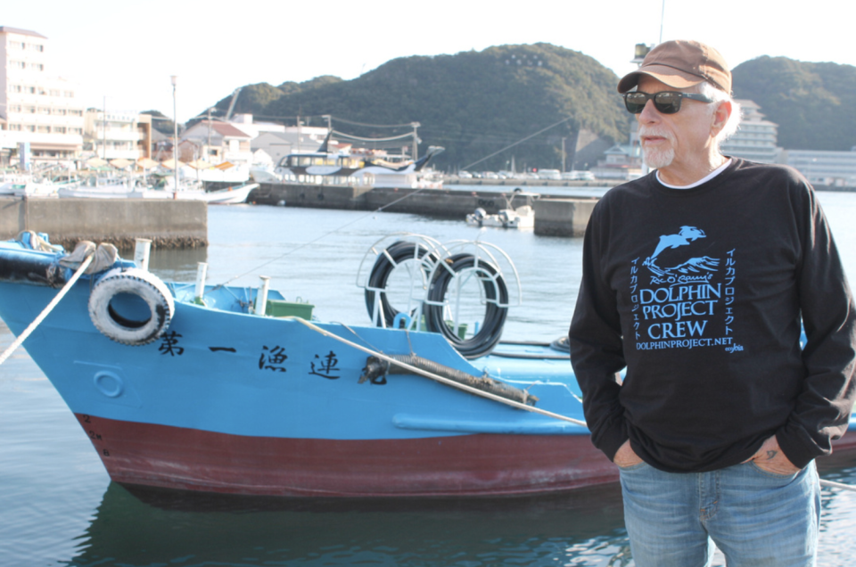 Ric O'Barry wears jeans and a Dolphin Project wind-cheater. The ocean and a boat with Japanese characters on it is in the background.