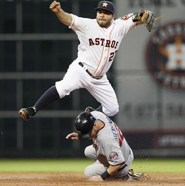 Houston Astros second baseman Jose Altuve (27) turns a double play as Minnesota Twins' Chris Herrmann (12) attempts to break up the throw in the second inning of a baseball game Monday, Sept. 2, 2013, in Houston. (AP Photo/Bob Levey)