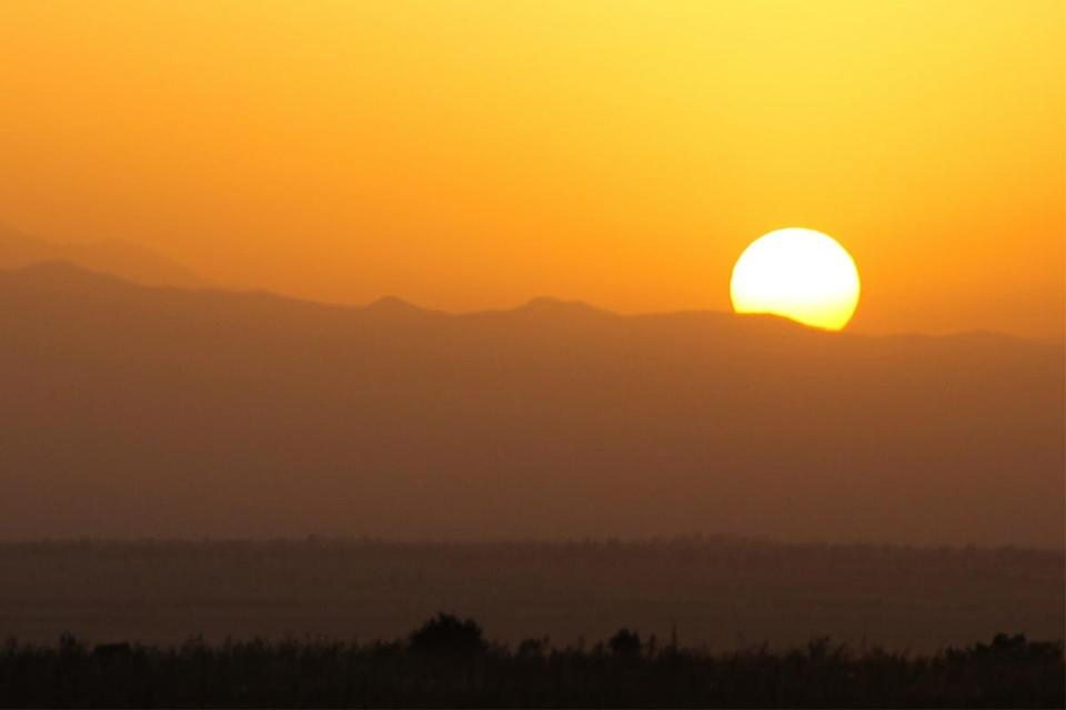 The sun rises over the mountains. In the Pacific Northwest, a heat dome has led to record-breaking temperatures.