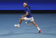 Greece's Stefanos Tsitsipas plays the ball back between his legs in his doubles match with compatriot Michail Pervolarakis against Australia's John Peers and Luke Saville in their ATP Cup match in Melbourne, Australia, Wednesday, Feb. 3, 2021. (AP Photo/Hamish Blair)