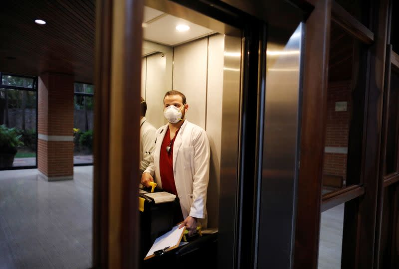 Venezuelan doctor Leonardo Acosta enters an elevator before visiting a patient suffering from the coronavirus disease (COVID-19) for home treatment, in Caracas