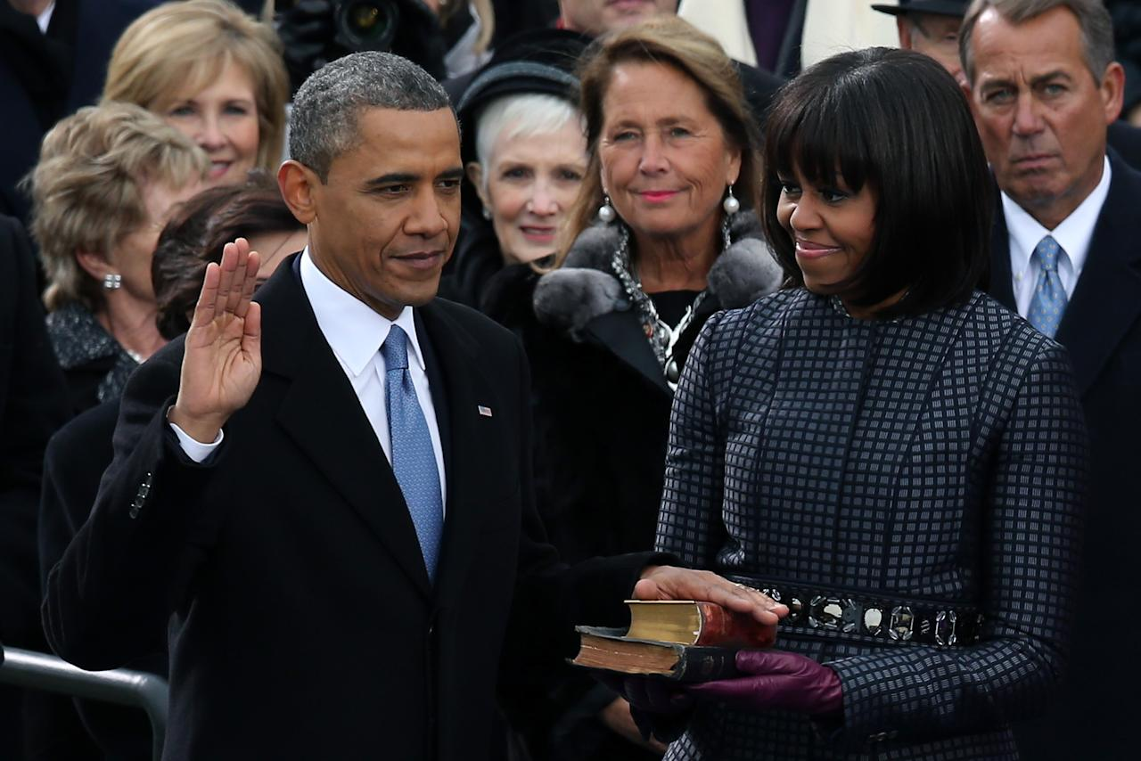 U.S. President Barack Obama is sworn in during the public ceremony as First lady Michelle Obama looks on during the presidential inauguration on the West Front of the U.S. Capitol January 21, 2013 in Washington, DC.   Barack Obama was re-elected for a second term as President of the United States.  (Photo by Alex Wong/Getty Images)