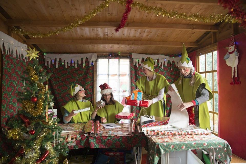 Four women dressed as Santa's elves wrap presents ready for Christmas.