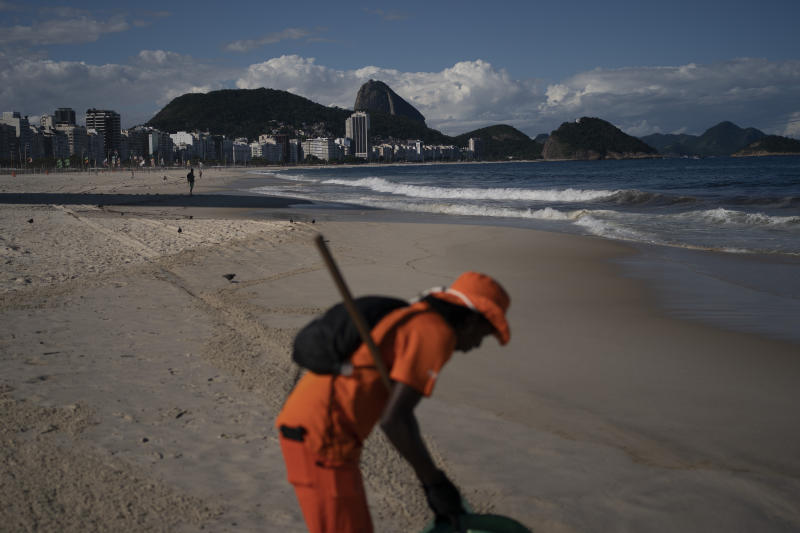"""Gloria Maria cleans the shore of an unusually empty Copacabana beach backdropped by the Sugar Loaf Mountain in Rio de Janeiro, Brazil, Thursday, March 26, 2020, as people stay indoors to help contain the spread of the new coronavirus. The 41-year-old city worker said that in her 10 years of work cleaning the beach, she never saw an empty beach on a sunny Thursday. """"It's terrible, people are dying in Europe due this virus,"""" she added. (AP Photo/Leo Correa)"""