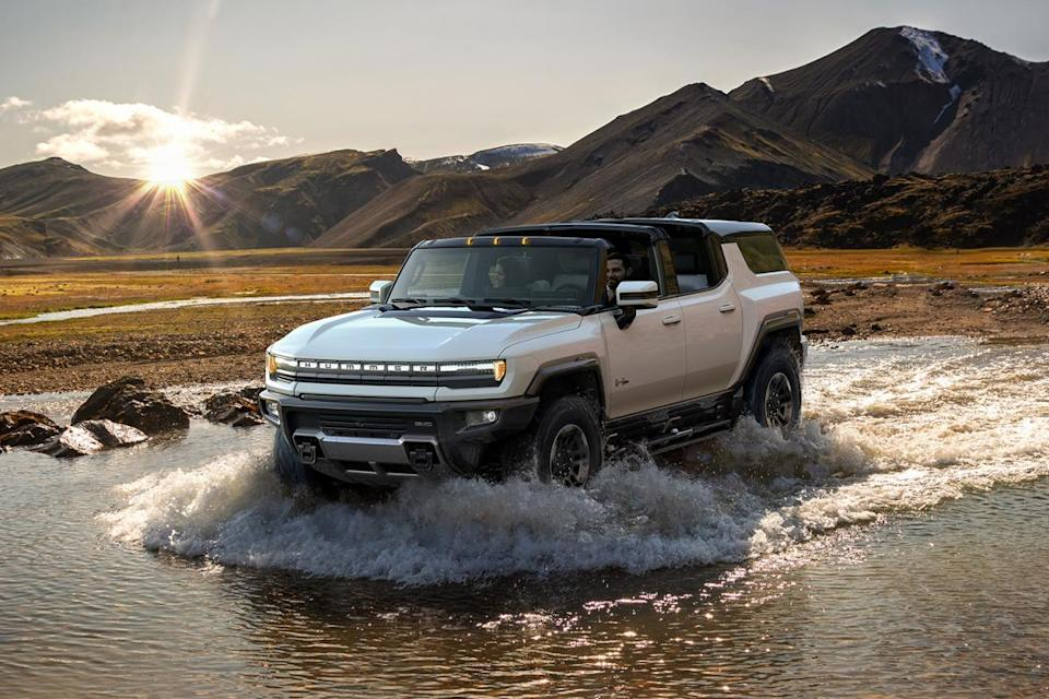 The 2024 GMC Hummer EV SUV fording a stream in the wilderness