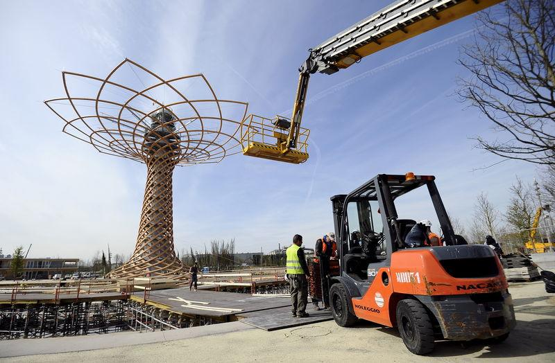 """Workers stand near the 37-meter """"The Tree of Life"""" at the Expo 2015 work site near Milan"""