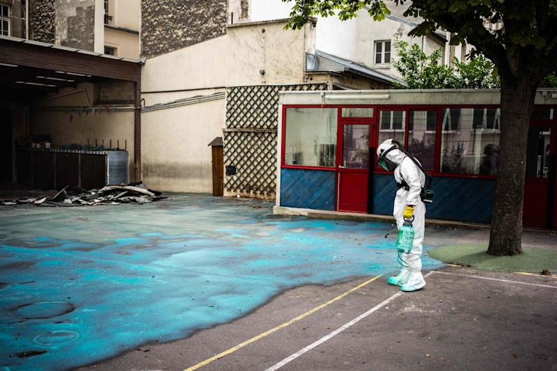 A worker sprays a gel on the ground to absorb lead as he takes part in a clean-up operation at Saint Benoit school (AFP/Getty Images)