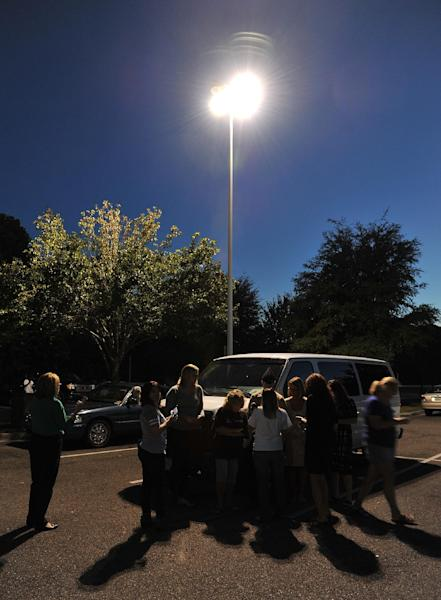 Friends and family huddle under a street light in the Jacksonville International Airport courtesy parking lot using phones to communicate with passengers stuck in the airport or in other cities Tuesday, Oct. 1, 2013, in Jacksonville, Fla. The airport was evacuated after authorities found two suspicious packages. (AP Photo/The Florida Times-Union, Bruce Lipsky)