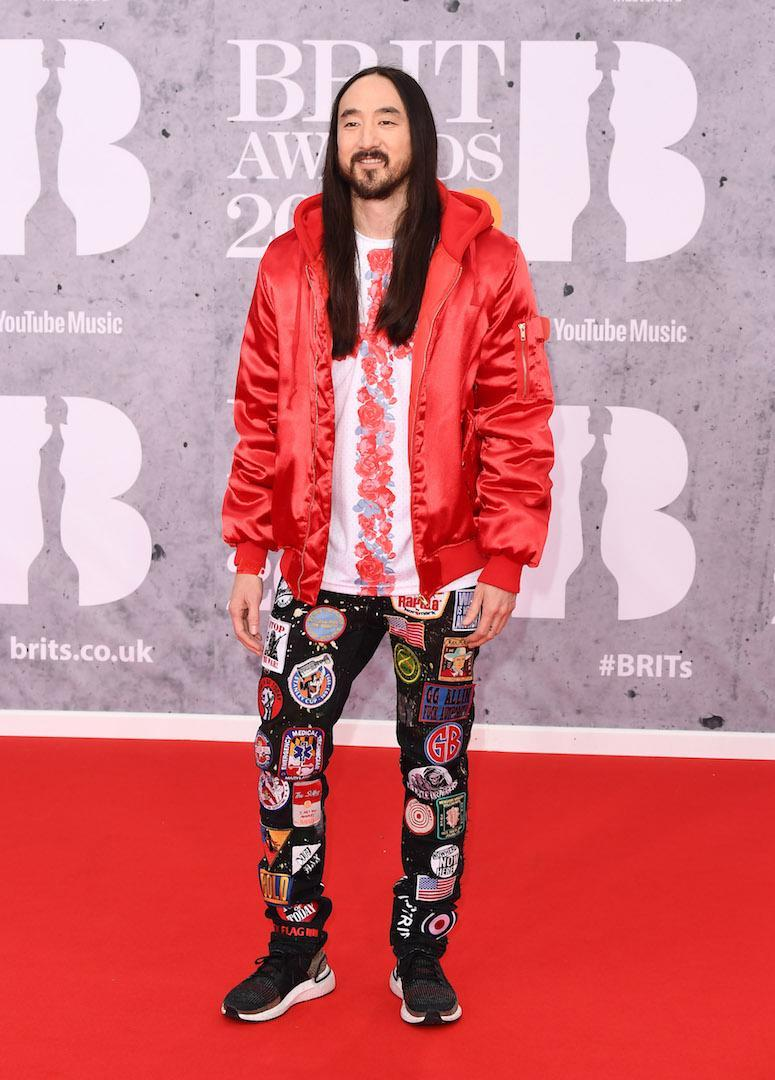 <p>Wearing a red bomber and patterned trousers. <em>[Photo: Getty]</em> </p>
