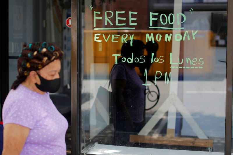 FILE PHOTO: A pedestrian passes a notice for a food pantry in Chelsea