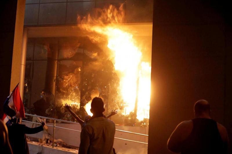 Protestors set fire to the Congress building during a demonstration against a possible change in the law (REUTERS)