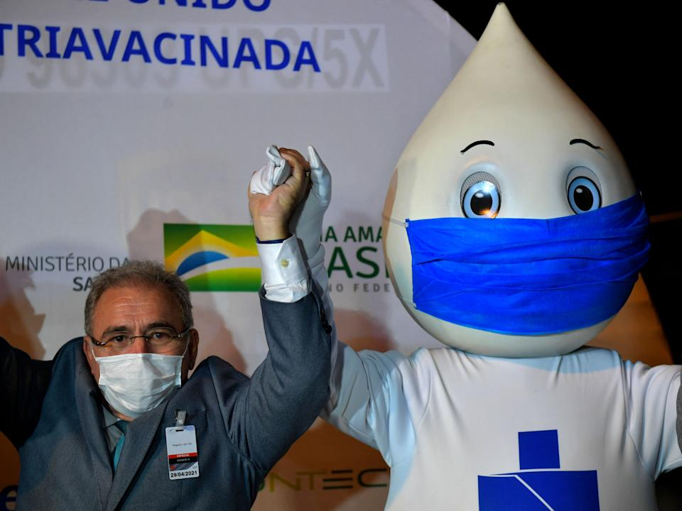 Brazilian Health Minister Marcelo Queiroga holds hands with Ze Gotinha, the mascot of the vaccination campaign in Brazil, upon the arrival of a container with 1,000,000 doses of the Pfizer-BioNTech vaccine against COVID-19 at the Viracopos International Airport in Campinas, some 100 km from Sao Paulo, Brazil on April 29, 2021. - Brazil received Thursday a first lot of 1,000,000 doses of the Pfizer-BioNTech vaccine developed by US drugmaker Pfizer and BioNTech of Germany. (Photo by NELSON ALMEIDA / AFP) (Photo by NELSON ALMEIDA/AFP via Getty Images)