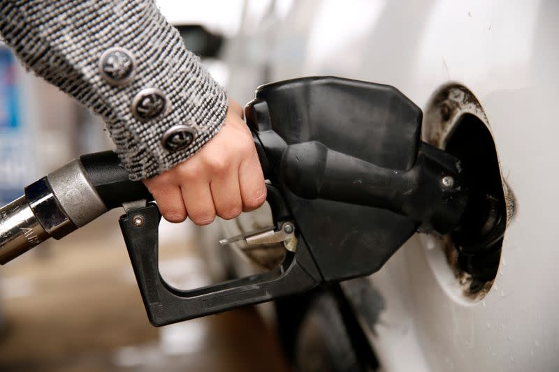A woman pumps gas at a station in Falls Church