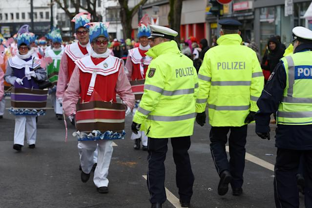 <p>German police walk past dressed-up people during a carnival parade on Rose Monday on Feb. 12, 2018 in Duesseldorf, western Germany. (Photo: Patrik Stollarz/Getty Images) </p>