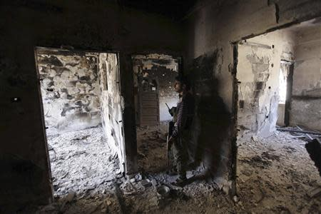 A Free Syrian Army fighter holds a weapon as he stands inside a room in Deir al-Zor