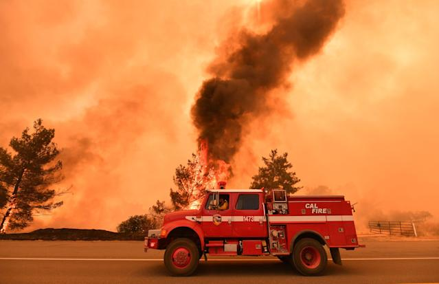 <p>Firefighters work to control a fire as flames from the County Fire jump across Highway 20 near Clearlake Oaks, Calif. on July 1, 2018. (Photo: Josh Edelson/AFP/Getty Images) </p>