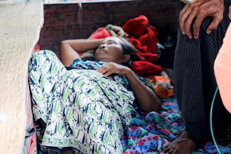 FILE PHOTO: Relative sits with a coronavirus disease (COVID-19) patient in the town of Kale, Sagaing Region, Myanmar