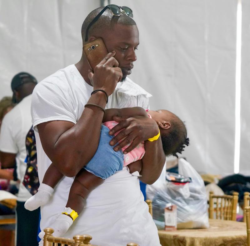 Hurricane Dorian evacuee Cecil Grant, 31, cradles his sleeping daughter, Yalissa, 7 months, while he makes a phone call at a shelter in Nassau, Bahamas, a day after fleeing their longtime home on Abaco after the storm destroyed their house and much of the surrounding community.