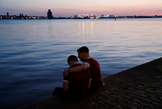 Soccer Football - Liverpool fans watch the Champions League Final - Liverpool, Britain - May 26, 2018 Liverpool fans looks dejected as they sit beside the river Mersey near Albert Dock REUTERS/Peter Nicholls