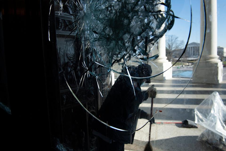 A worker cleans broken glass from one of the entrances to the US Capitol after a pro-Trump mob broke into the building during protests the previous day January 7, 2021, in Washington, DC. (Photo by Brendan Smialowski / AFP) (Photo by BRENDAN SMIALOWSKI/AFP via Getty Images)