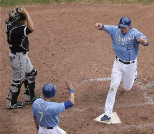 Kansas City Royals' Elliot Johnson (23) and David Lough (7) celebrate after scoring on a fielding error hit into by Alcides Escobar during the eighth inning of a baseball game against the Chicago White Sox, Sunday, June 23, 2013, in Kansas City, Mo. (AP Photo/Charlie Riedel)
