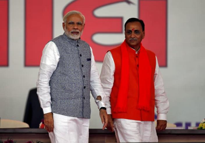 FILE PHOTO: Vijay Rupani walks with India's PM Modi after taking his oath as the chief minister of the western state of Gujarat during a swearing-in ceremony at Gandhinagar