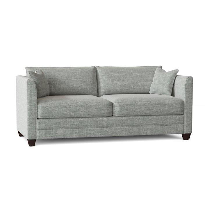 """Gone are the days of throwing out your back yanking the mattress out from the sofa, because Wayfair's Sarah sofa bed (which is available for custom upholstery) has arrived. This stylish sofa bed can support up to 500 pounds courtesy of its sturdy wood legs and coil-spring mattress. Plus, the chic upholstery (which also comes in a whopping 25 colorways) offers a welcoming 1970s-like touch. Did we mention it comes with two super-soft <a href=""""https://www.architecturaldigest.com/story/best-throw-pillows?mbid=synd_yahoo_rss"""" rel=""""nofollow noopener"""" target=""""_blank"""" data-ylk=""""slk:throw pillows"""" class=""""link rapid-noclick-resp"""">throw pillows</a>? $920, Wayfair. <a href=""""https://www.wayfair.com/furniture/pdp/sarah-77-square-arm-sofa-bed-w003048341.html?"""" rel=""""nofollow noopener"""" target=""""_blank"""" data-ylk=""""slk:Get it now!"""" class=""""link rapid-noclick-resp"""">Get it now!</a>"""