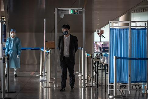A man wearing a protective mask walking through thermal scanners at the security check at the Capital International Airport in Beijing on 17 March 2020. Photo: EPA-EFE