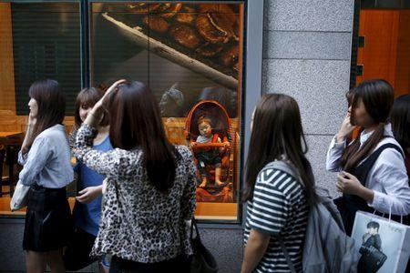 """Participants arrive to take part in TV program """"The Body Show"""" at a gym as a baby in a stroller looks on in Seoul, September 19, 2015. REUTERS/Kim Hong-Ji"""