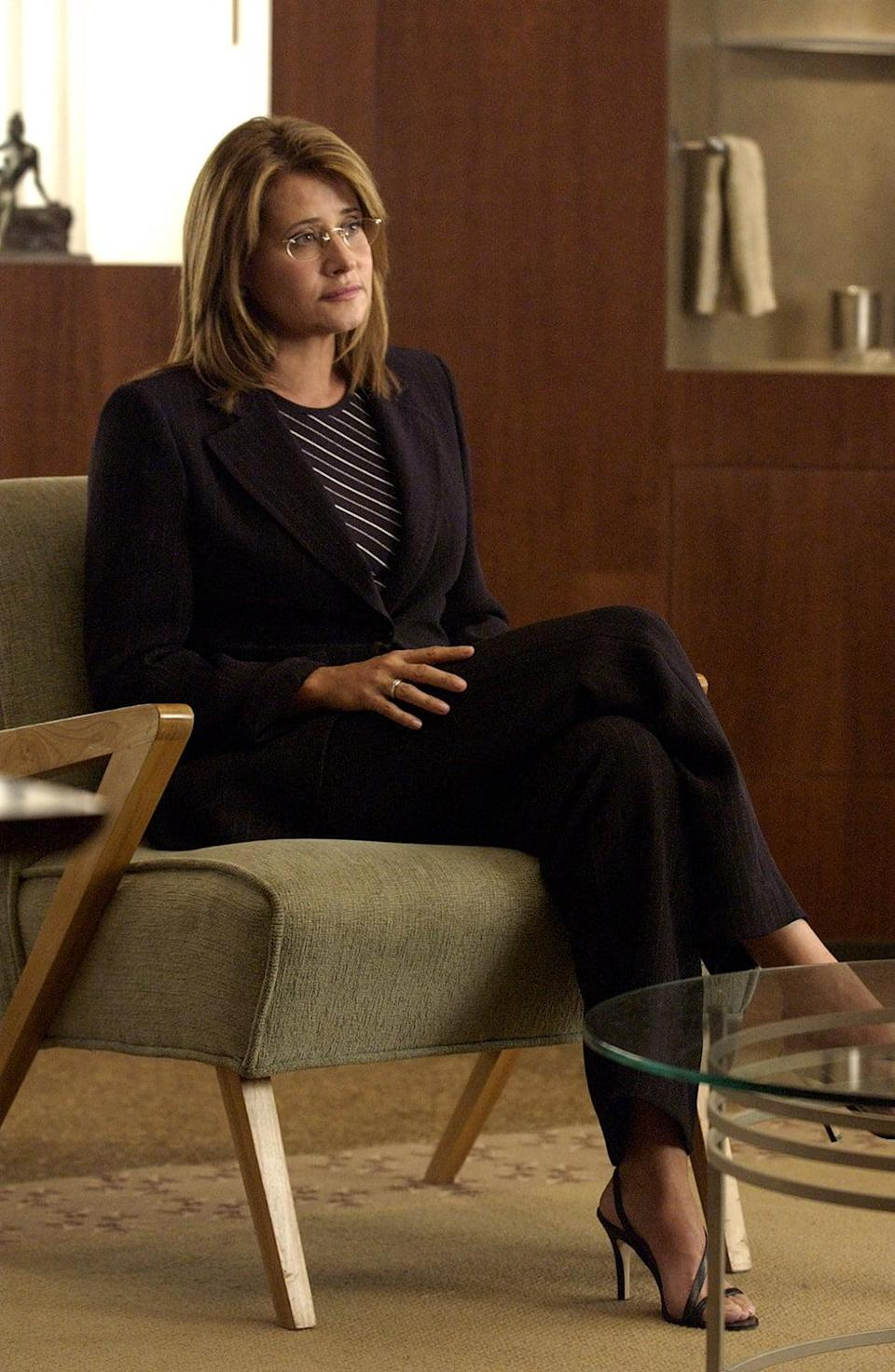 """<p>Although she's a fellow Italian, Dr. Jennifer Melfi is merely an observer and holds nothing in common with Tony and his world. Unlike other women depicted in <strong>The Sopranos</strong>, Melfi is reserved, never gives in to Tony's advances, and doesn't take opportunities to get """"even."""" Her commitment to her practice is reflected in her lackluster wardrobe - filled with monochromatic sets - in contrast to Adriana and Carmela's ostentatious outfits. Today, the uniform <a href=""""https://www.popsugar.com/fashion/How-Wear-Suits-Flat-Sandals-46153319"""" class=""""link rapid-noclick-resp"""" rel=""""nofollow noopener"""" target=""""_blank"""" data-ylk=""""slk:dress code is back"""">dress code is back</a>, but in a more casual fashion, found to be paired with sandals instead of strappy heels.</p>"""