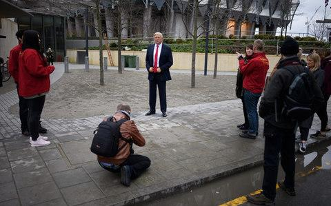 People take photographs of a model of US President Donald Trump - Credit: Getty