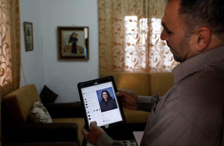 Uncle of Rashida Tlaib, the first Palestinian-American woman to be elected to the U.S. Congress, shows her picture on a tablet, in Beit Ur Al-Fauqa, in the occupied West Bank
