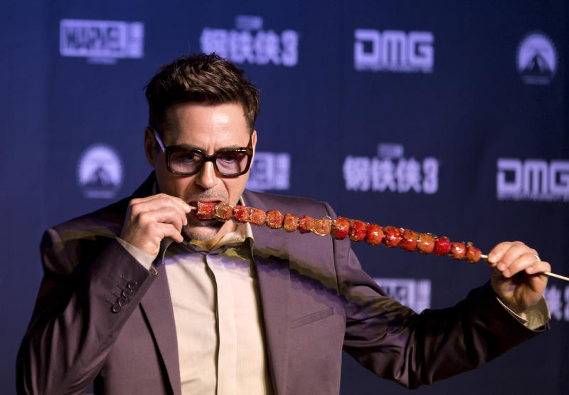 """U.S. actor Robert Downey Jr. tries out """"bingtanghulu,"""" a traditional Chinese snack, during a world premiere event of his new movie """"Iron Man 3"""" at a Beijing hotel Saturday, April 6, 2013. (AP Photo/Andy Wong)"""