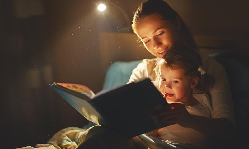 Woman reading storybook to child