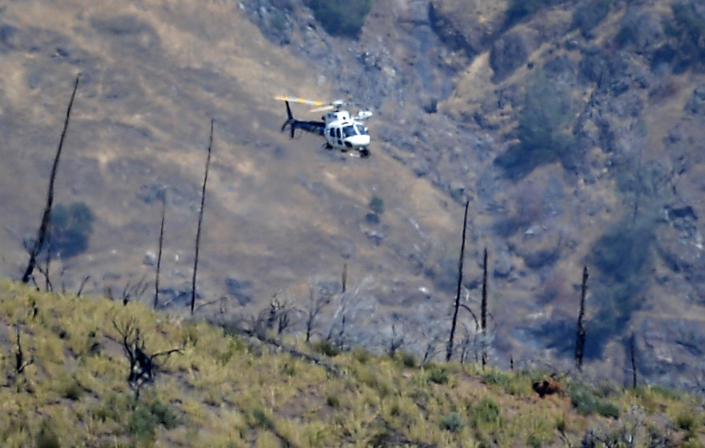 A helicopter hovers over a remote area northeast of the town of Mariposa, California on August 18, 2021. According to the Mariposa County Sheriff's Office, the area is reported to be where a family and their dog were found dead. / Credit: Craig Kohlruss/AP