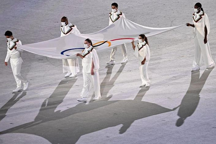 <p>The Olympic flag is carried by six masked individuals during the ceremony.</p>