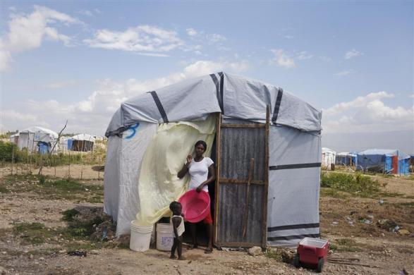 Haitian Mirlene Similien, 22, stands with her child outside her tent, at a camp for people who were affected by the 2010 earthquake, outside Port-au-Prince, August 23, 2012.