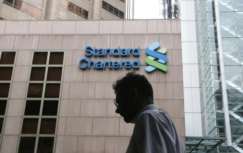A man walks past the Standard Chartered bank building in Hong Kong Tuesday, Aug. 7, 2012. Shares in Standard Chartered PLC dropped sharply on Tuesday as investors reacted to U.S. charges that the bank was involved in laundering money for Iran. (AP Photo/Kin Cheung)