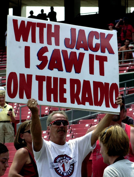 FILE - In this June 18, 2002, file photo, Marty Prather, of Springfield, Mo., holds a sign in rememberance of Jack Buck, the legendary St. Louis Cardinals broadcaster, at Bush Stadium in St. Louis. Unlike basketball or football or other major sports where the action is nonstop, baseball provides many opportunities for broadcasters to fill with stories and personal anecdotes. They weave in updates about their gardens and their travel experiences and their everyday adventures.(AP Photo/Diane L. Wilson, File)