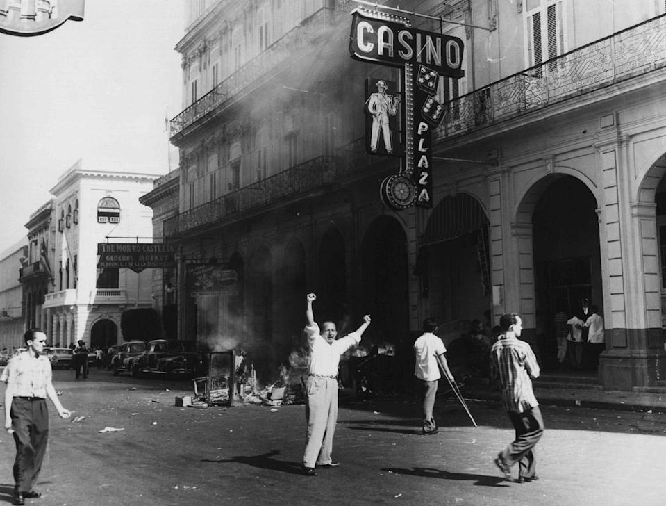 <p>People burn tables and roulette wheels outside the Plaza Hotel Casino in Old Havana, Cuba, in Jan. 1959, shortly after revolutionary leader Fidel Castro gained power. On Jan. 1, 1959, dictator Fulgencio Batista fled Cuba and Castro's rebels took power. (AP Photo/Fernando Lezcano) </p>