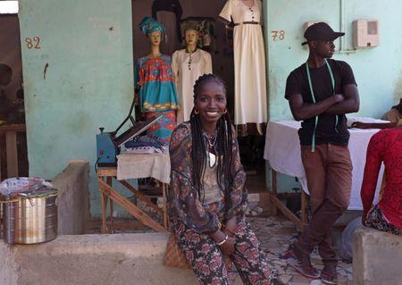 Fatou Kine poses for a photo outside her shop in Guediawaye, Senegal April 16, 2018. REUTERS/Mikal McAllister/Files