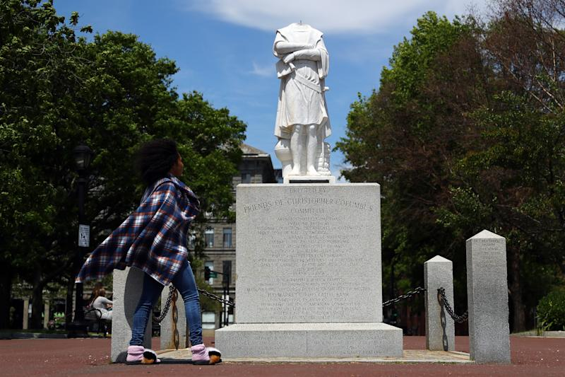 A woman looks at a statue depicting Christopher Columbus which had its head removed at Christopher Columbus Waterfront Park on June 10, 2020 in Boston, Massachusetts. The statue was beheaded overnight and is scheduled to be removed by the City of Boston. (Tim Bradbury/Getty Images)