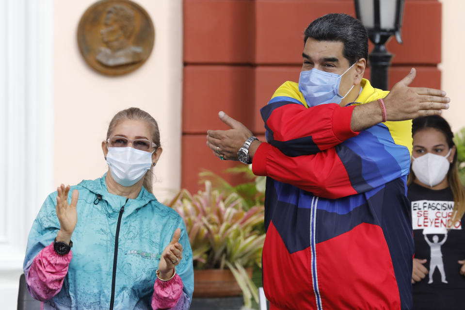 Venezuelan President Nicolas Maduro gestures a hug to supporters during an event with his wife Cilia Flores marking Youth Day at Miraflores presidential palace in Caracas, Venezuela, Friday, Feb. 12, 2021, amid the COVID-19 pandemic. The annual holiday commemorates young people who accompanied heroes in the battle for Venezuela's independence. (AP Photo/Ariana Cubillos)