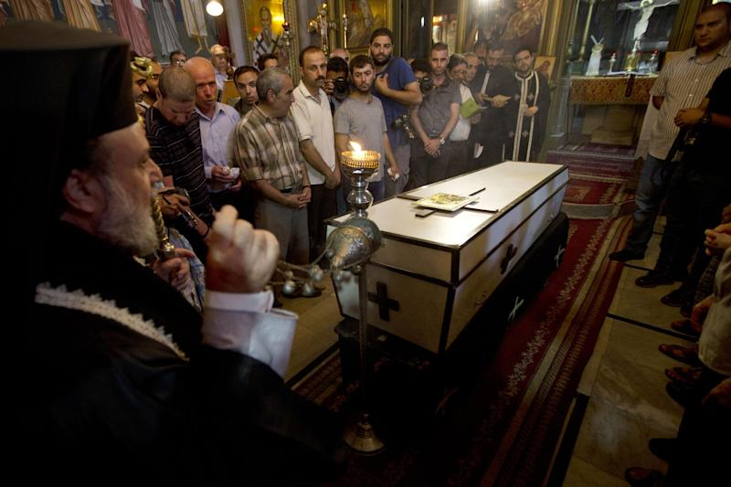 Palestinian relatives and friends of Jalila Ayyad, a Christian woman whose body was found under the rubble of her home after an Israeli airstike, mourn over her coffin during her funeral on July 27, 2014 in Gaza City (AFP Photo/Mahmud Hams)